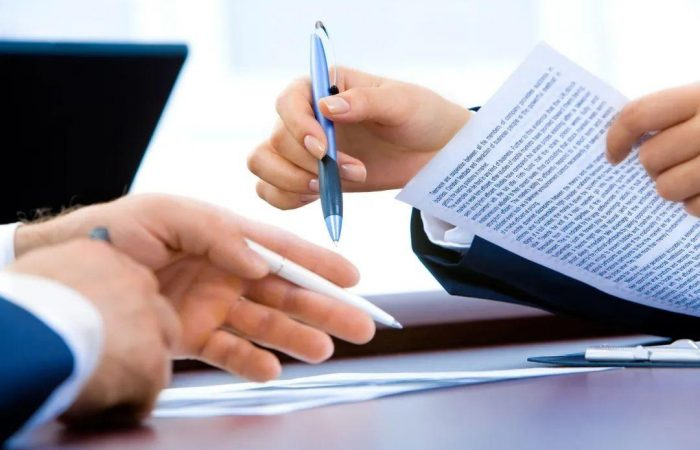 two hands ready to sign the document